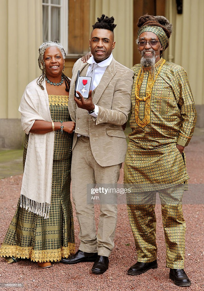 British soul singer Omar Lyefook stands between his parents Sonia and Byron as he poses with his Member of the British Empire (MBE) medal after it was presented to him by the Prince of Wales during the Investiture ceremony at Buckingham Palace in central London on January 25, 2013. AFP PHOTO/POOL/JOHN STILLWELL