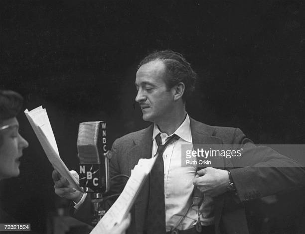 British stage and screen actor David Niven adjusts his suspender as he reads a script and stands before a WNBC microphone while an unidentified woman...