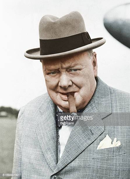 British statesman Winston Churchill in 1949 smoking one of his beloved cigars as he leaves the plane that brought him back from a continental holiday...