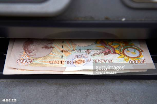 British sterling ten pound banknotes are seen in an automated teller machine in this posed photograph taken outside a branch of the British bank...