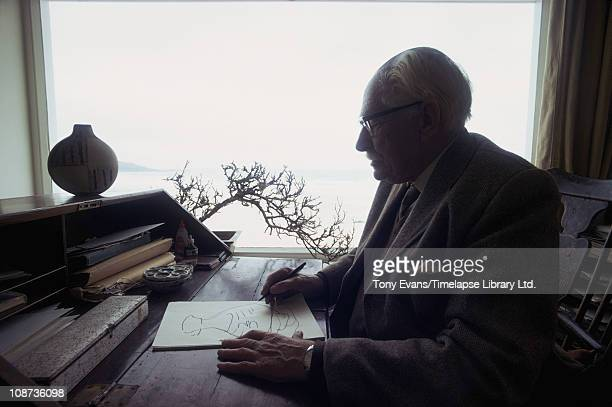 British studio potter Bernard Leach drawing at his desk in St Ives with pot that featured in Royal Mail commemorative stamp 1974