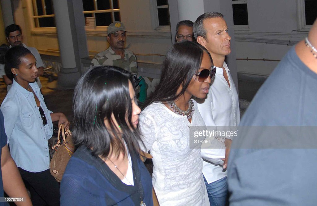 British supermodel Naomi Campbell (2R) and her boyfriend Vladimir Doronin (R) walk with their security in Jodhpur on November 8, 2012. A star-studded guest list including Kate Moss and Bob Geldof gathered in India on November 7 for a lavish 50th birthday party arranged by supermodel Naomi Campbell for her Russian billionaire boyfriend.