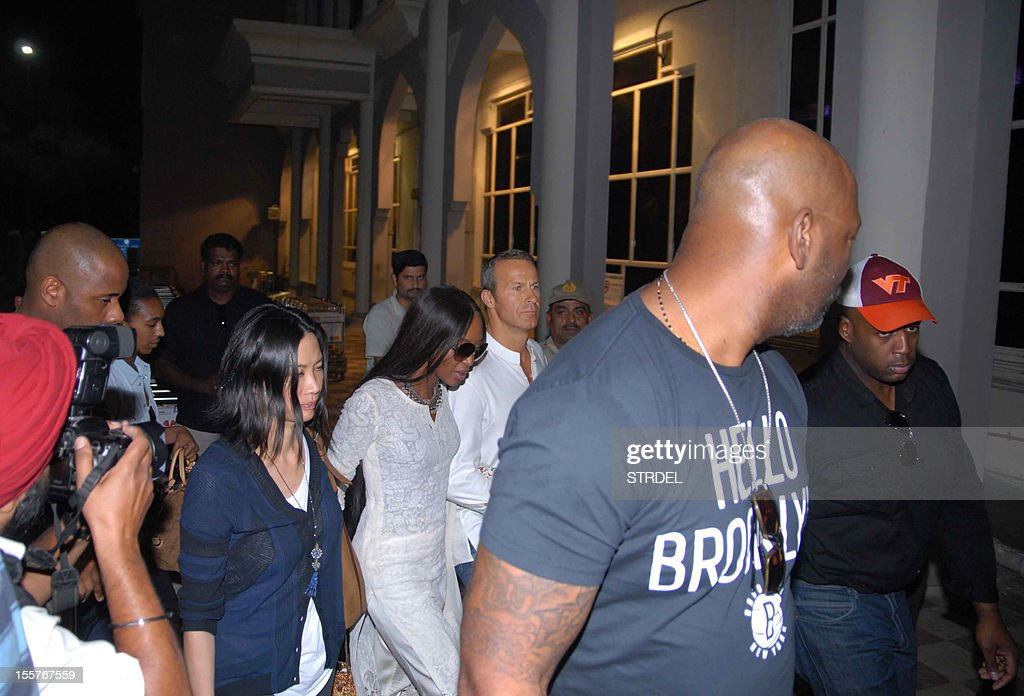 British supermodel Naomi Campbell (C) and her boyfriend Vladimir Doronin (3R) walk with their security in Jodhpur on November 8, 2012. A star-studded guest list including Kate Moss and Bob Geldof gathered in India on November 7 for a lavish 50th birthday party arranged by supermodel Naomi Campbell for her Russian billionaire boyfriend.