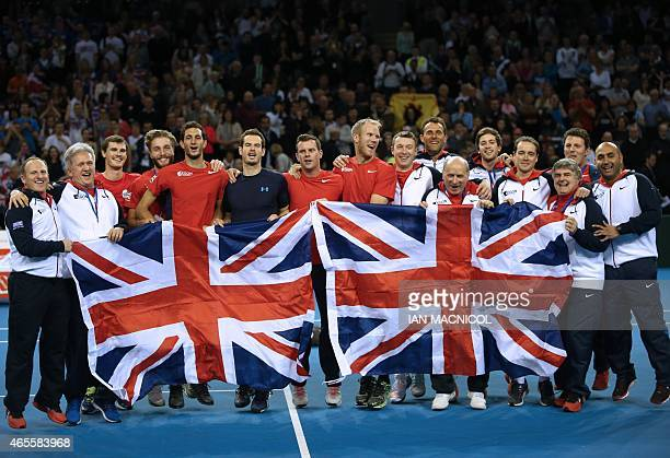 British team members celebrate with Union flags on the court after Murray's victory over John Isner of US on day three of the Davis Cup World Group...
