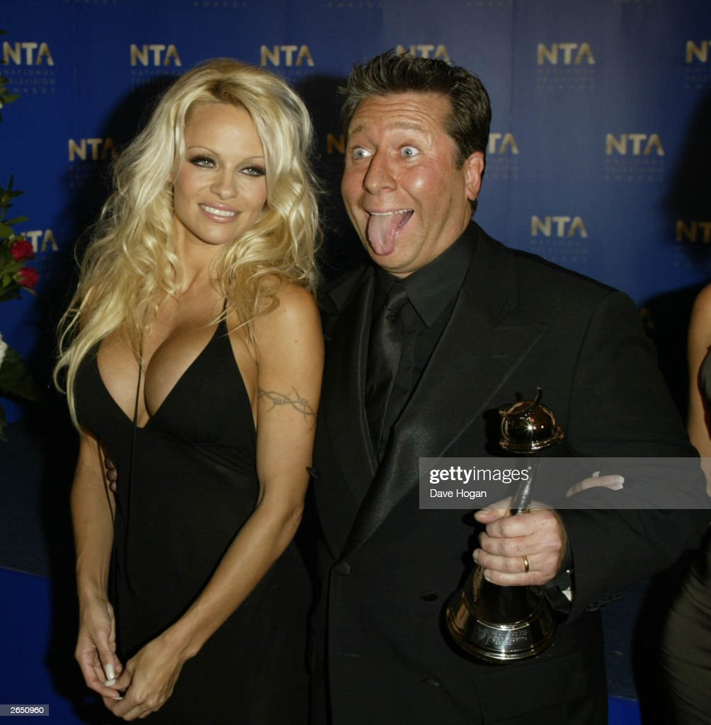 British television and radio presenter Neil 'Dr' Fox and American actress <a gi-track='captionPersonalityLinkClicked' href=/galleries/search?phrase=Pamela+Anderson&family=editorial&specificpeople=171759 ng-click='$event.stopPropagation()'>Pamela Anderson</a> celebrate after winning the award for 'Most Popular Entertainment Programme' for the programme 'Pop Idol' at the National TV Awards party at the Royal Albert Hall on October 15, 2002 in London.