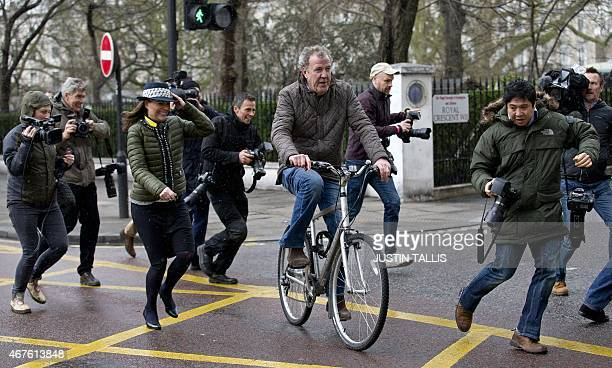 British television presenter Jeremy Clarkson is surrounded by media personnel as he leaves his home on a bicycle in London on March 26 2015 The BBC...
