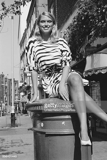 British television presenter on the game show 'Treasure Hunt' Anneka Rice pictured sitting on top of a postbox on Upper St Martins Lane in London on...