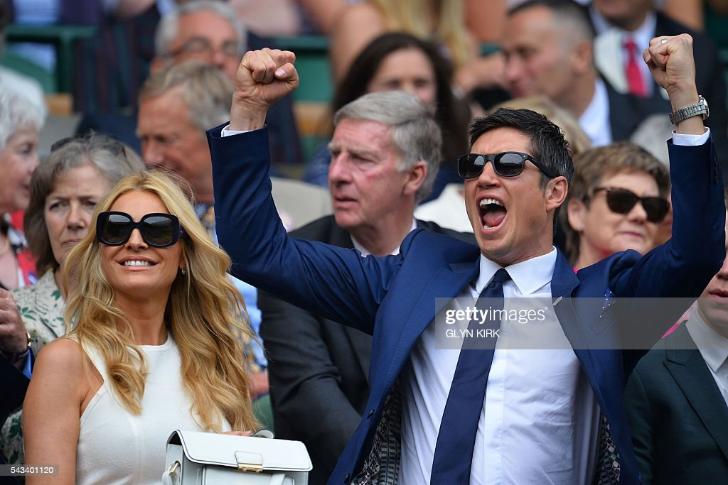 British television presenter Vernon Kay (R) gestures in the royal box next to wife presenter and model Tess Daly (L) as they prepare to watch US player Serena Williams play Switzerland's Amra Sadikovic on Centre Court during their women's singles first round match on the second day of the 2016 Wimbledon Championships at The All England Lawn Tennis Club in Wimbledon, southwest London, on June 28, 2016. / AFP / GLYN