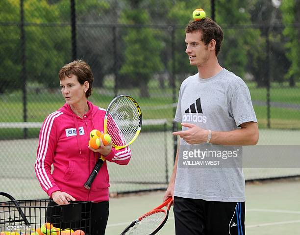 British tennis player Andy Murray balances a ball on his head as he and his mother Judy a tennis coach give lessons to young tennis players in...