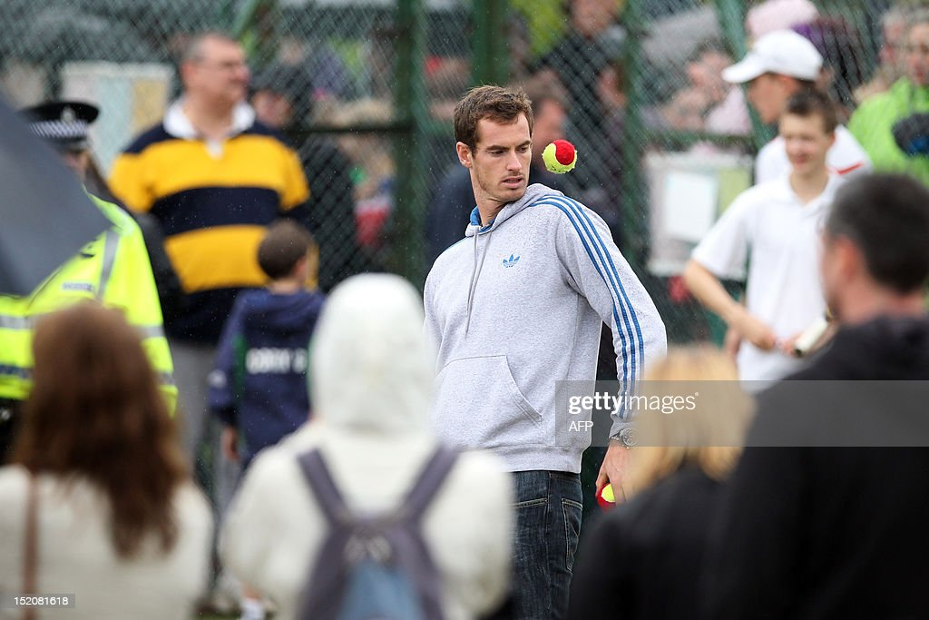 British tennis player Andy Murray juggles with tennis balls as he meets children at his local tennis club after walking through the centre of Dunblane, Scotland on September 16, 2012, following his victory in the US Open tennis tournament and gold medal in the London 2012 Olympic Games. Andy Murray, the first British man to win a Grand Slam title in 76 years, received a rapturous welcome in his Scottish home town on Sunday, but admitted that his golden summer was giving him nightmares. AFP PHOTO / IAN MACNICOL