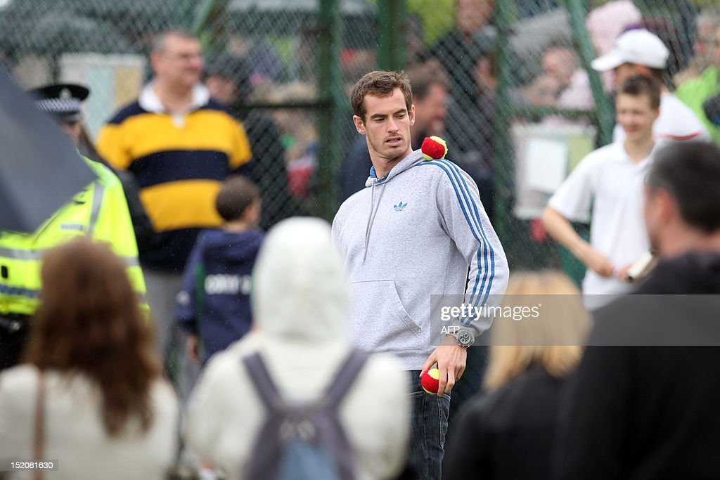 British tennis player Andy Murray juggles with tennis balls as he meets children at his local tennis club after walking through the centre of Dunblane, Scotland on September 16, 2012, following his victory in the US Open tennis tournament and gold medal in the London 2012 Olympic Games. Andy Murray, the first British man to win a Grand Slam title in 76 years, received a rapturous welcome in his Scottish home town on Sunday, but admitted that his golden summer was giving him nightmares.