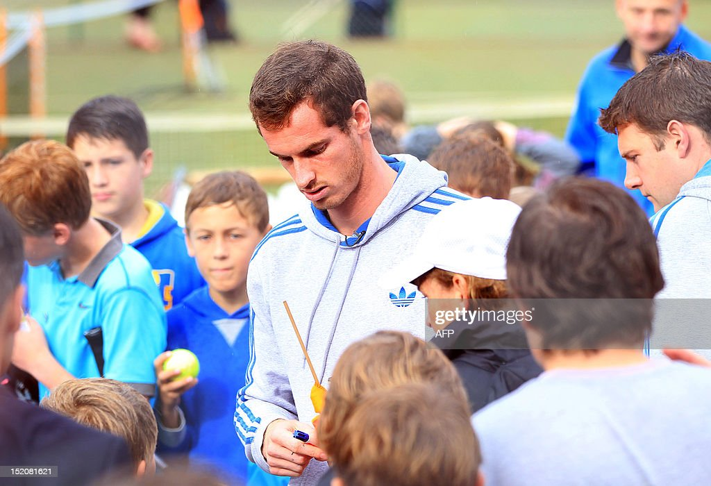 British tennis player Andy Murray meets children at his local tennis club after walking through the centre of Dunblane, Scotland on September 16, 2012, following his victory in the US Open tennis tournament and gold medal in the London 2012 Olympic Games. Andy Murray, the first British man to win a Grand Slam title in 76 years, received a rapturous welcome in his Scottish home town on Sunday, but admitted that his golden summer was giving him nightmares. AFP PHOTO / IAN MACNICOL