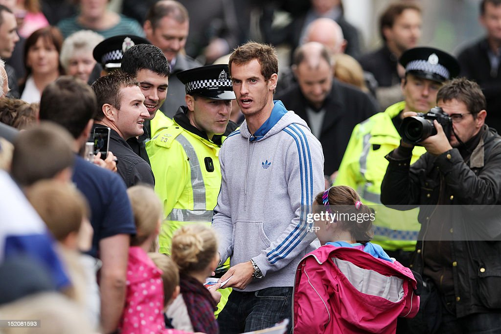 British tennis player Andy Murray meets with fans in the centre of Dunblane, Scotland on September 16, 2012, following his victory in the US Open tennis tournament and gold medal in the London 2012 Olympic Games. Andy Murray, the first British man to win a Grand Slam title in 76 years, received a rapturous welcome in his Scottish home town on Sunday, but admitted that his golden summer was giving him nightmares. AFP PHOTO / IAN MACNICOL