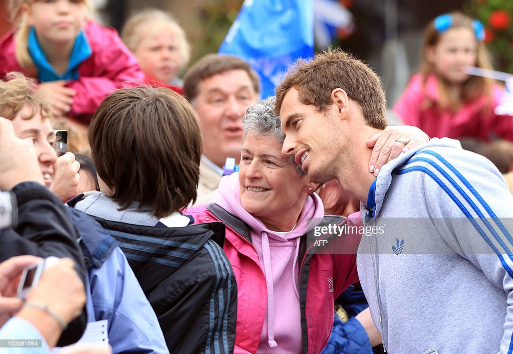 British tennis player Andy Murray poses for a photo with fans in the centre of Dunblane, Scotland on September 16, 2012, following his victory in the US Open tennis tournament and gold medal in the London 2012 Olympic Games. Andy Murray, the first British man to win a Grand Slam title in 76 years, received a rapturous welcome in his Scottish home town on Sunday, but admitted that his golden summer was giving him nightmares.