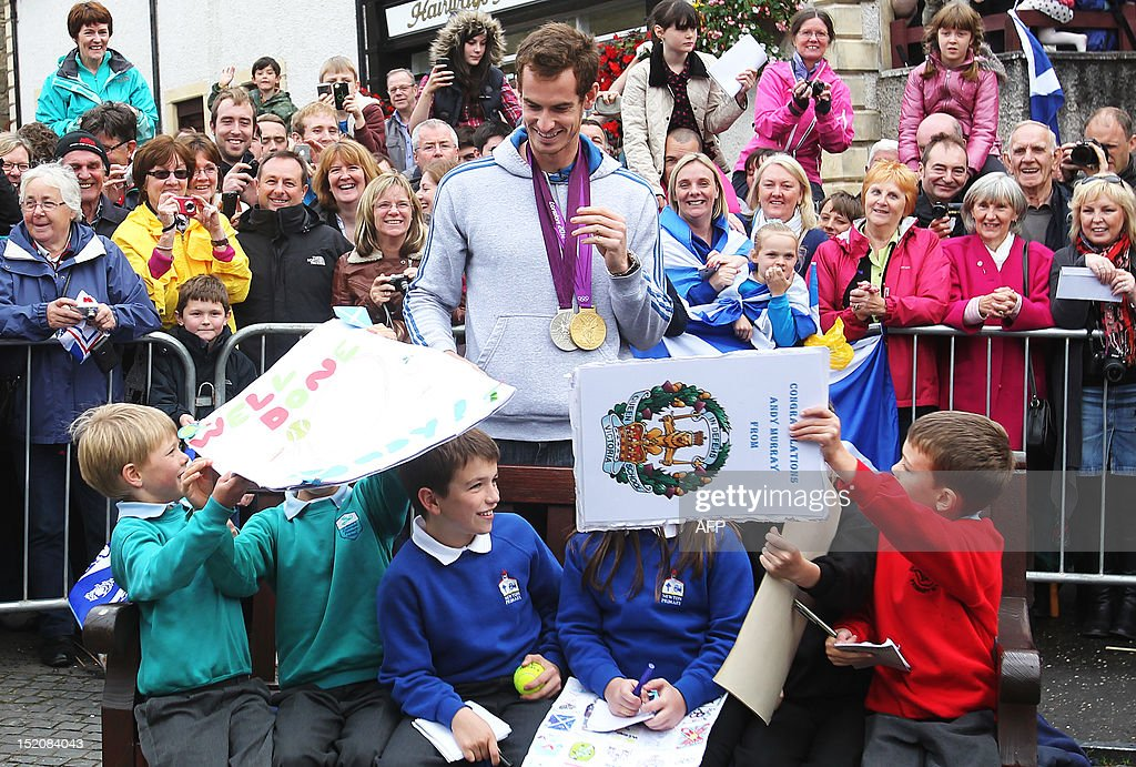 British tennis player Andy Murray poses with local children in the centre of Dunblane, Scotland on September 16, 2012, following his victory in the US Open tennis tournament and gold medal in the London 2012 Olympic Games. Andy Murray, the first British man to win a Grand Slam title in 76 years, received a rapturous welcome in his Scottish home town on Sunday, but admitted that his golden summer was giving him nightmares. AFP PHOTO / IAN MACNICOL