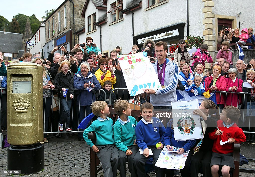 British tennis player Andy Murray poses with local children next to Royal Mail golden post box in the centre of Dunblane, Scotland on September 16, 2012, following his victory in the US Open tennis tournament and gold medal in the London 2012 Olympic Games. Andy Murray, the first British man to win a Grand Slam title in 76 years, received a rapturous welcome in his Scottish home town on Sunday, but admitted that his golden summer was giving him nightmares.