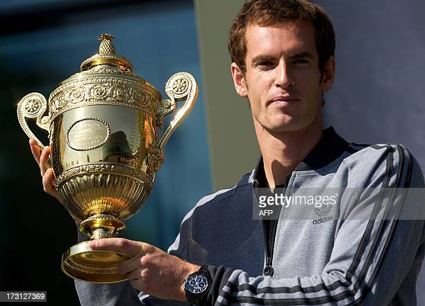 British tennis player Andy Murray poses with the 2013 Wimbledon trophy at the All England Club in Wimbledon southwest London on July 8 a day after he...