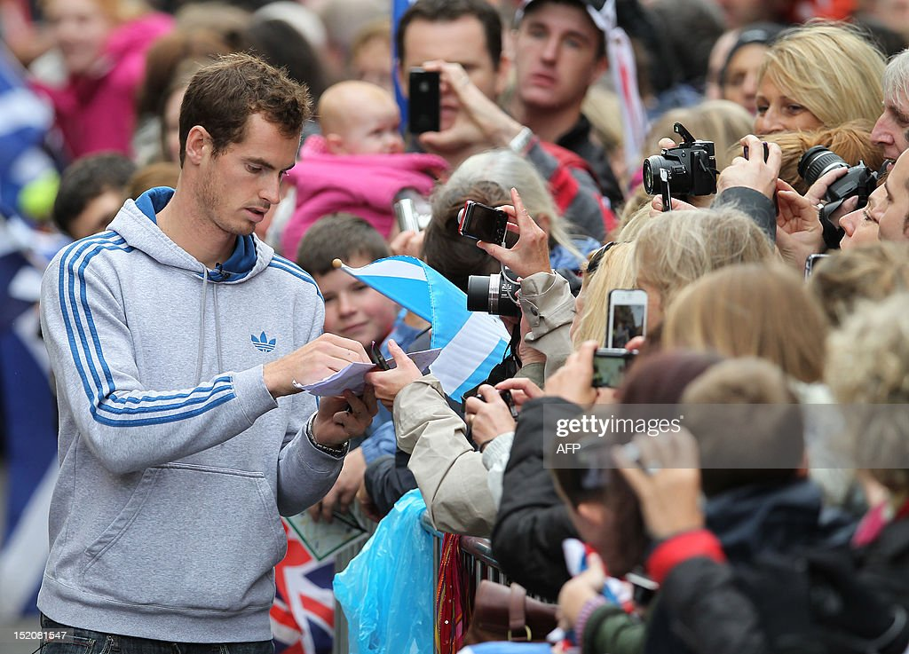 British tennis player Andy Murray signs autographs as he meets with fans in the centre of Dunblane, Scotland on September 16, 2012, following his victory in the US Open tennis tournament and gold medal in the London 2012 Olympic Games. Andy Murray, the first British man to win a Grand Slam title in 76 years, received a rapturous welcome in his Scottish home town on Sunday, but admitted that his golden summer was giving him nightmares. AFP PHOTO / IAN MACNICOL