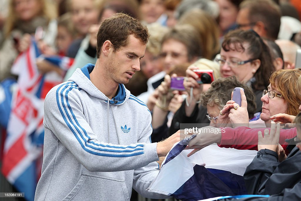British tennis player Andy Murraysigns autographs as he meets with fans in the centre of Dunblane, Scotland on September 16, 2012, following his victory in the US Open tennis tournament and gold medal in the London 2012 Olympic Games. Andy Murray, the first British man to win a Grand Slam title in 76 years, received a rapturous welcome in his Scottish home town on Sunday, but admitted that his golden summer was giving him nightmares. AFP PHOTO / IAN MACNICOL