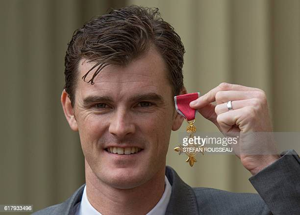 British tennis player Jamie Murray poses at Buckingham Palace in London after he received his Officer of the Order of the British Empire for services...