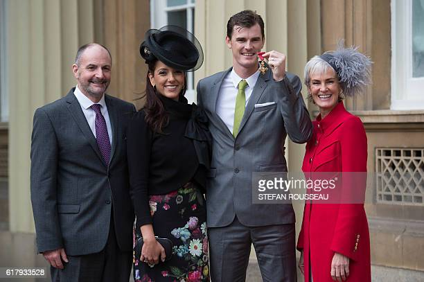 British tennis player Jamie Murray poses with his father William wife Alejandra Gutierrez and mother Judy at Buckingham Palace in London after he...