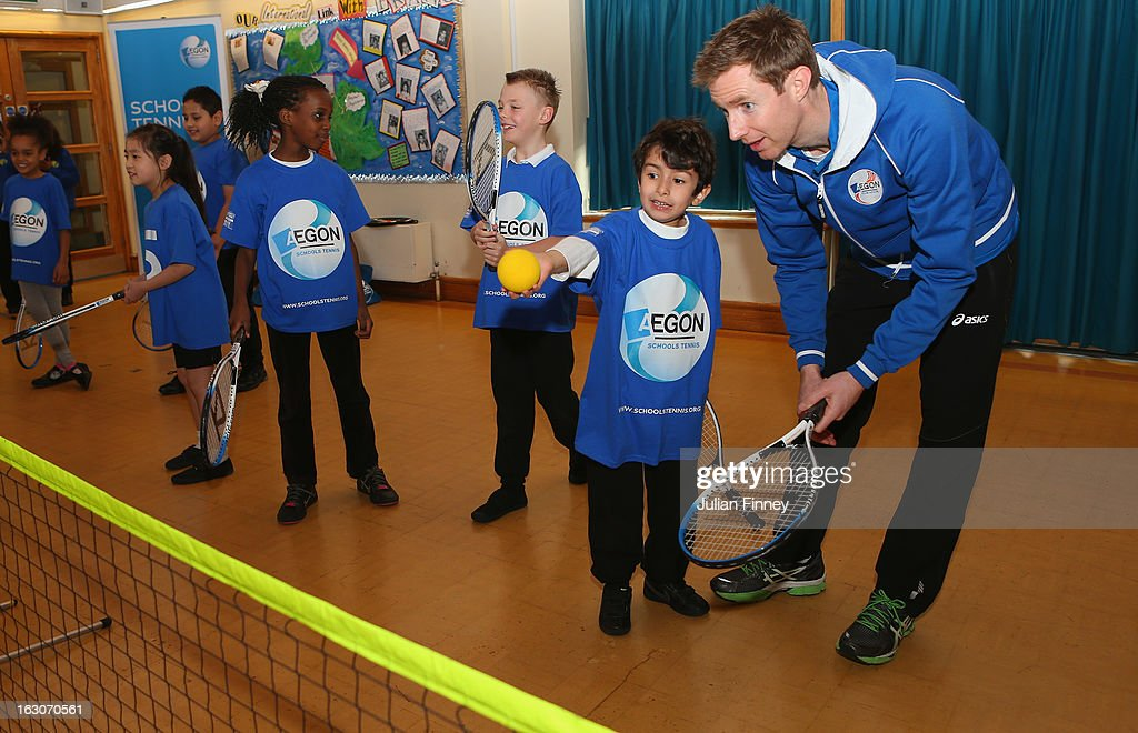 British tennis player Jonny Marray helps a child at the Britannia Village Primary School on March 4, 2013 in London, England. Aegon Schools Tennis Programme names Britannia Village Primary School, Newham as the 15,000th School beneficiary today which coincides with World Tennis Day.