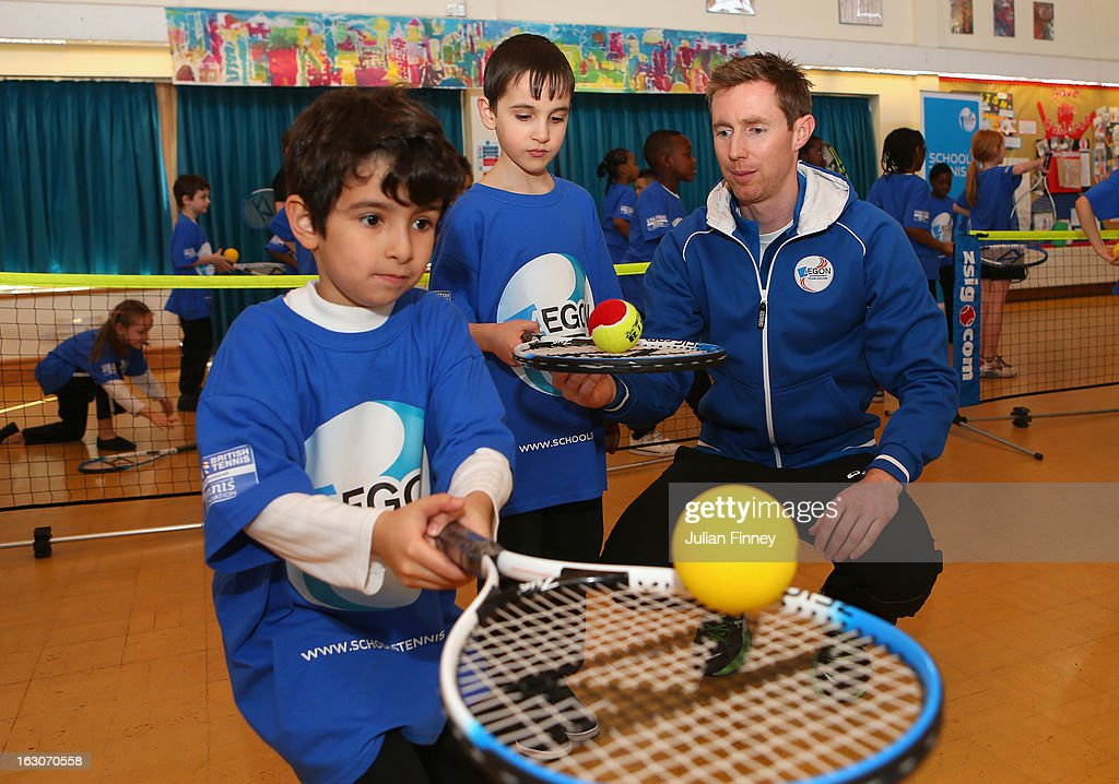 British tennis player Jonny Marray helps children play tennis at the Britannia Village Primary School on March 4, 2013 in London, England. Aegon Schools Tennis Programme names Britannia Village Primary School, Newham as the 15,000th School beneficiary today which coincides with World Tennis Day.