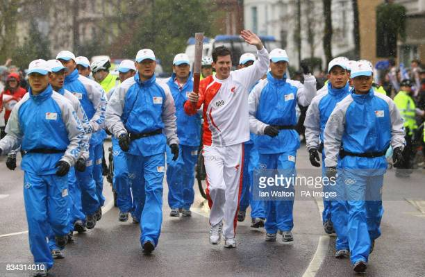 British tennis player Tim Henman carries the Olympic torch during its relay journey across London on its way to the lighting of the Olympic cauldron...