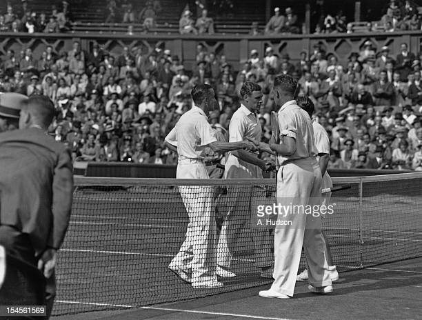 British tennis players Raymond Tuckey and Pat Hughes congratulate Jack Crawford and Adrian Quist of Australia on their victory in a Davis Cup...