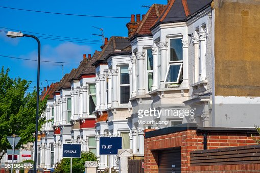 British terraced houses in London with estate agent boards : Stock Photo