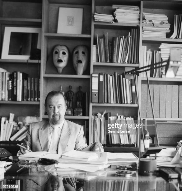 British theatre director Sir Peter Hall in his office circa 1980 Two ancient tragedy masks are visible on the shelves behind his head