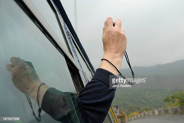 British tourist snaps a photo from the window of the Toy Train as it makes its way to Darjeeling The Darjeeling Himalayan Railway commonly known as...