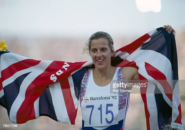 British track and field athlete Sally Gunnell of the Great Britain team celebrates with the national flag after crossing the finish line in first...