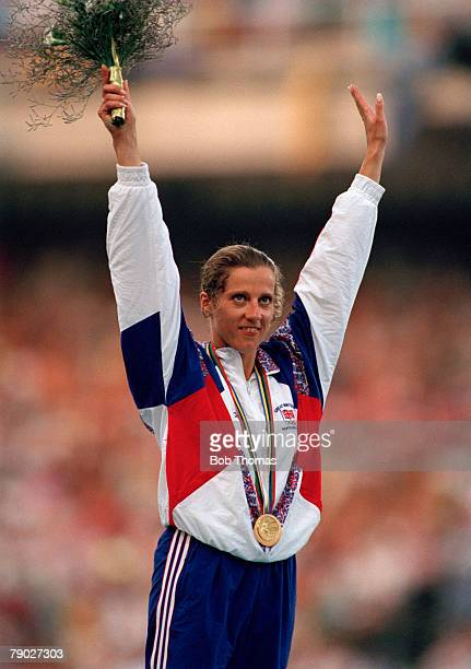 British track and field athlete Sally Gunnell of the Great Britain team raises her arms in the air in celebration on the medal podium after crossing...