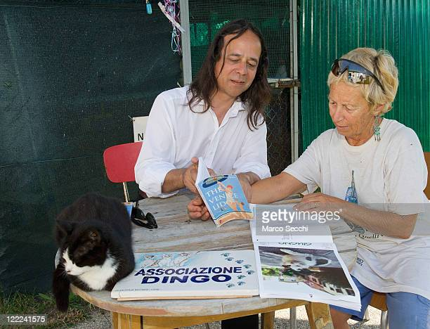 British travel writer Robin Saikia shows his latest book to a Dingo association volunteer on August 27 2011 in Venice Italy Dingo is the...