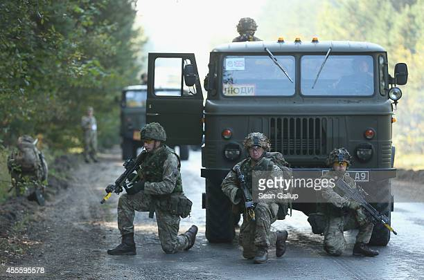 British troops of the Light Dragoons guard a convoy on the third day of the 'Rapid Trident' bilateral military exercises between the United States...