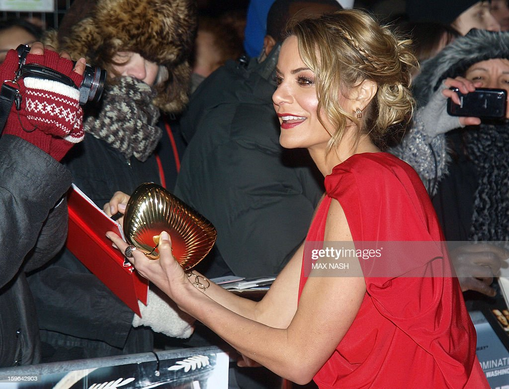 British tv presenter Charlotte Jackson signs her autograph for fans as she arrives to attend the UK Premiere of 'Flight' in London's Leicester Square on January 17, 2013.