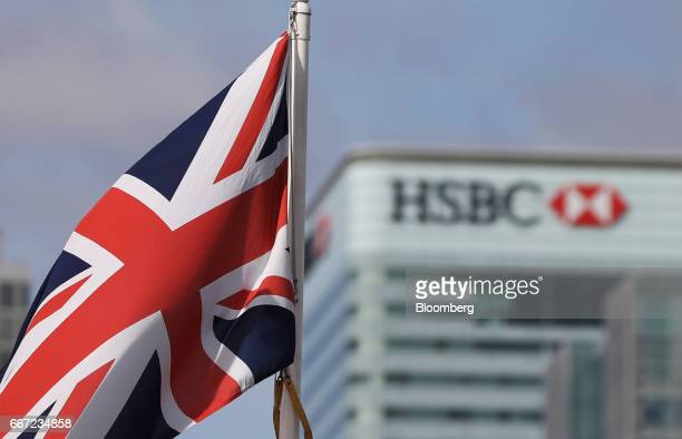 A British Union flag commonly known as the Union Jack flies in front of the HSBC Holdings Plc headquarter offices at Canary Wharf financial business...