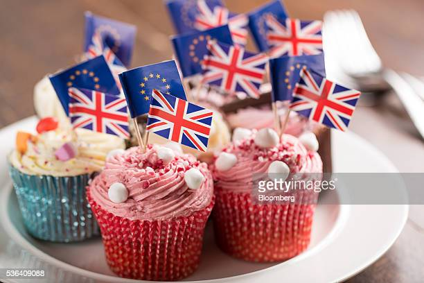 British Union Flags commonly known as Union Jacks and European Union flags stand on cocktail sticks from cupcakes sitting on a plate in this arranged...