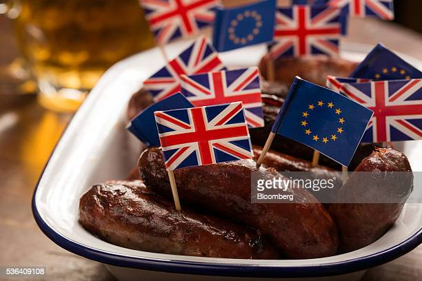 British Union Flags commonly known as Union Jacks and European Union flags stand on cocktail sticks in a dish of sausages on a table in this arranged...