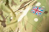 Union Jack / Union flag badge on a camouflage British army uniform. Text / writing space surrounding badge.