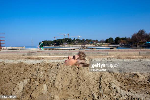 British university student buried in the sand on a beach near the Zelens Laguna resort in Porec He is on the inaugural ILOVETOUR to the town in...