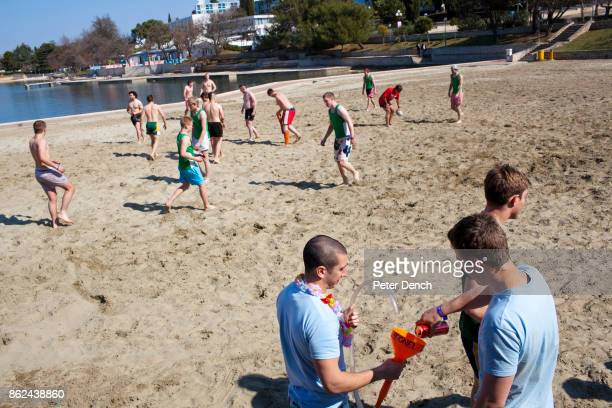 British university students prepare a beer bong on the beach where a game of rugby is in progress They are on the inaugural ILOVETOUR to the town of...