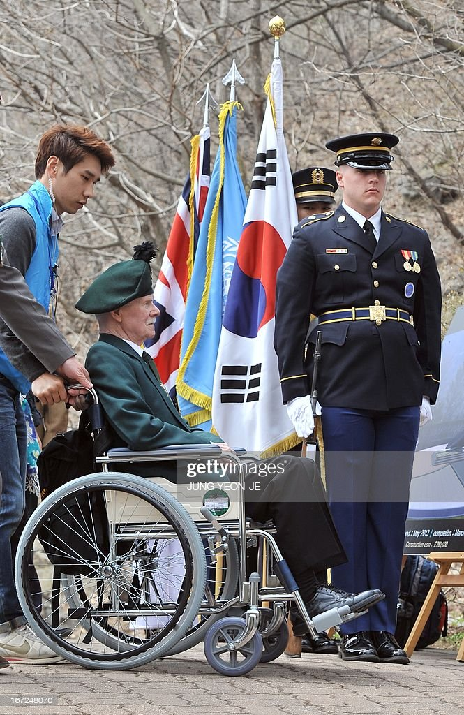 A British veteran (C) on a wheelchair, who fought alongside South Korea during the 1950-53 Korean War, passes by UN Command honour guards (R) during a ceremony to commemorate the 62nd anniversary of the action of British 29 Brigade at the battle of the Imjin River, at Gloster Valley in Paju, north of Seoul, 23 April 2013. The veterans laid the wreath at a British monument on Gloster Valley to remember some 800 British men killed in the fierce battle on 22-25 April 1951.
