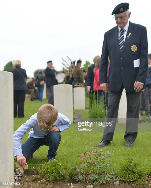 A British Veteran watches a local child placing a small cross at the grave at the end of the 72nd DDay anniversary service of thanksgiving and wreath...