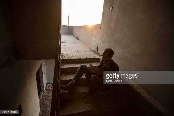 British volunteer fighter 'Macer Gifford' sits on his own in a stairwell near to the United States military base as he tries to get on the internet...