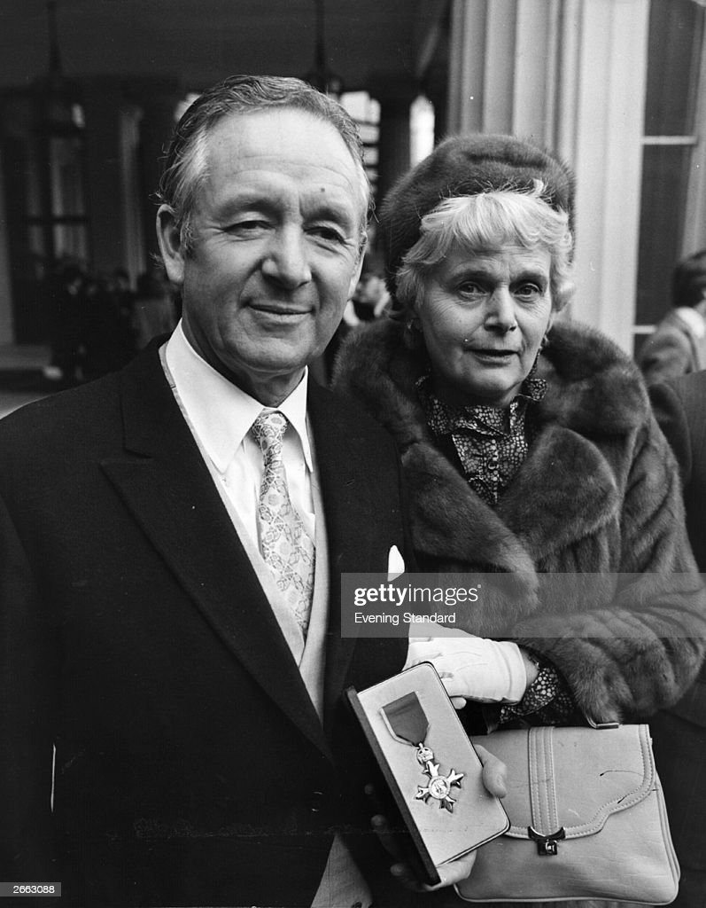 British writer James Herriot with his wife at Buckingham Palace after receiving his OBE.