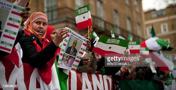 A Britishbased Somalilander holds up a poster bearing the image of Somaliland leader Ahmed Mohamed Silanyo as others wave the flag of the...