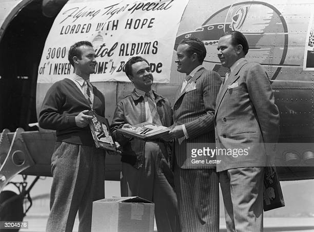 Britishborn actor and comedian Bob Hope holds a copy of his album 'Bob Hope 'I Never Left Home'' while three men pose with him on the tarmac in front...