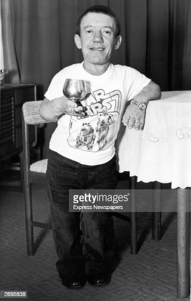 Britishborn actor Kenny Baker who played the robot R2D2 in director George Lucas's epic film 'Star Wars' smiling and leaning with his arm against a...